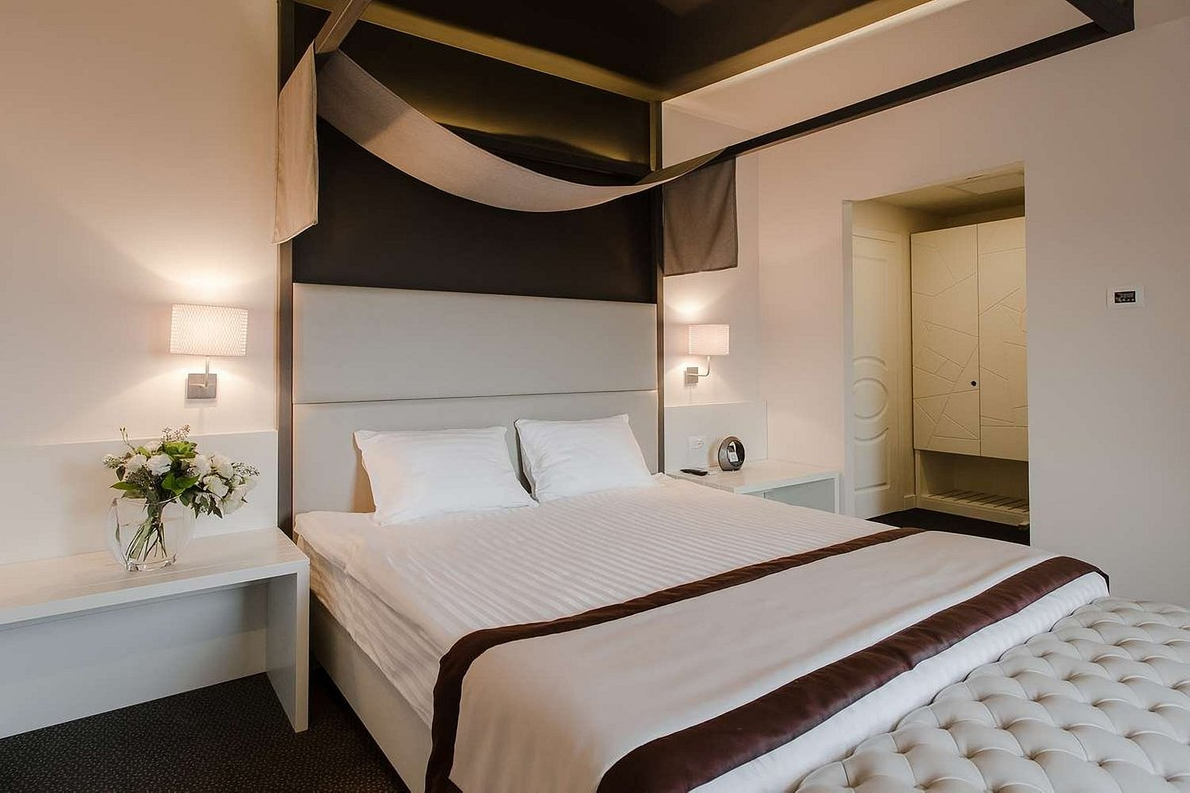 A bed with a soft headboard in a room at UNO Design Hotel Odessa Ukraine